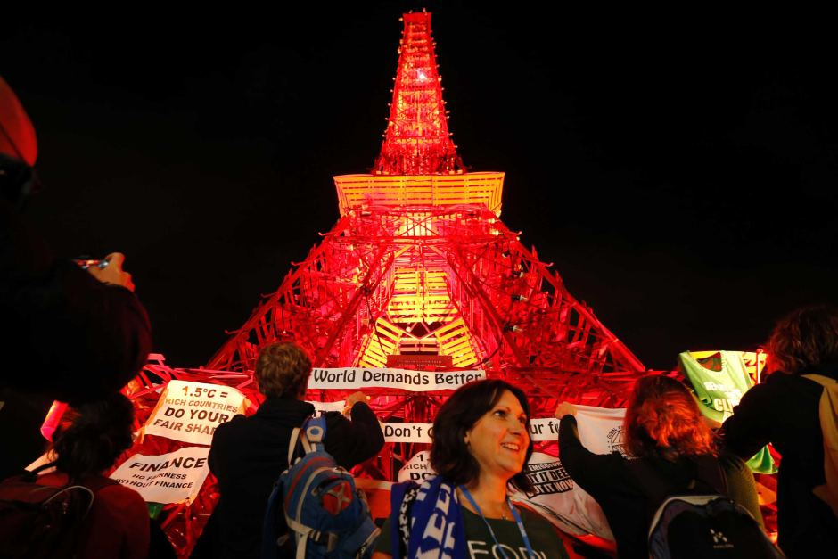 People demonstrate in front of a replica Eiffel Tower at COP21 as world leaders negotiate overnight. Source: ABC; Photo: Reuters, Stephane Mahe