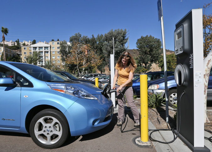 Angie Vorhies charged her electric car in San Diego in 2013. The city has committed to using 100 percent renewable energy, becoming the largest American municipality to do so. Source: The New York Times; Lenny Ignelzi/Associated Press